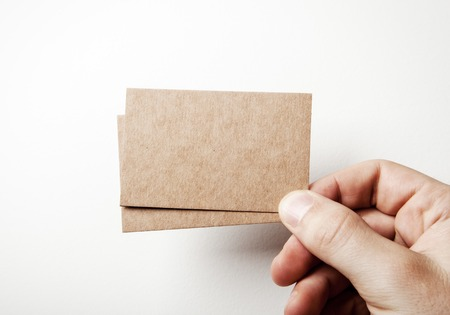 Photo pour Mock up of two blank business cards holding in a mans hand on the white background - image libre de droit