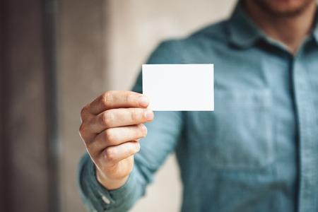 Photo pour Man holding business card on blurred background - image libre de droit