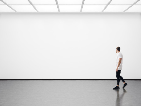 Photo pour A man walks on the exhibition hall and examines the gallery of the exhibition - image libre de droit