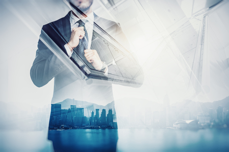 Close-up portrait of businessman straightens his own tie. Double exposure of panoramic city view at sunrise on the background