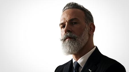 Stylish bearded man wearing trendy suit, stands against a white wall.