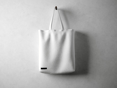 White and blank cotton textile bag holding, neutral background. horizontal