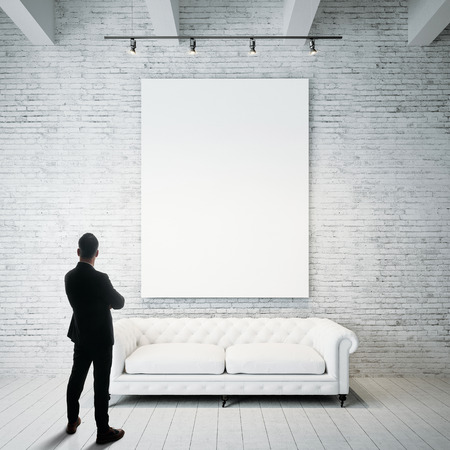 Photo for Man stands against holding blank white canvas and vintage classic sofa on the wood floor. Vertical - Royalty Free Image
