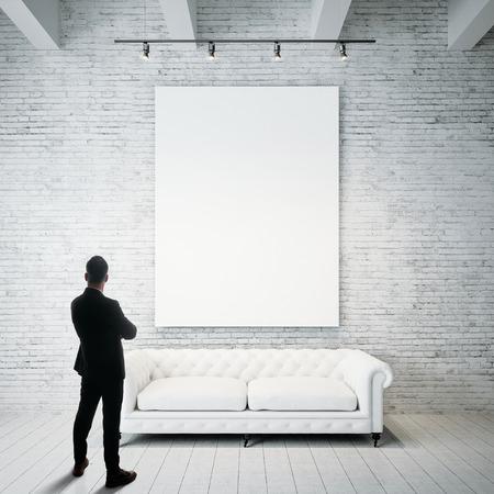 Foto de Man stands against holding blank white canvas and vintage classic sofa on the wood floor. Vertical - Imagen libre de derechos