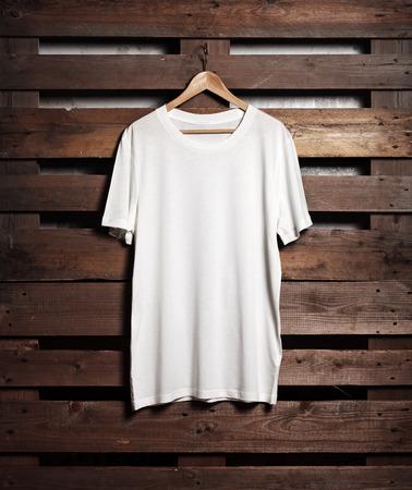 Photo pour Photo of blanc white tshirt hanging on wood background. Vertical - image libre de droit