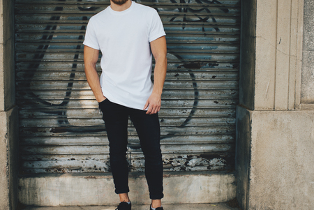 Photo of a bearded man wearing blank t-shirt, black jeans and standing opposite garage