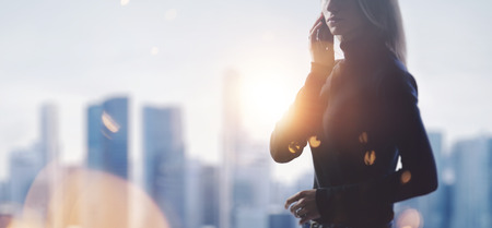 Foto per Portrait of young woman holding her smartphone in a hands. Blurred city on the background. - Immagine Royalty Free