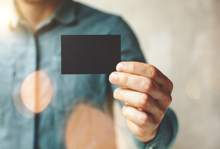 Photo pour Man wearing blue jeans shirt and showing blank black business card. Blurred background. Horizontal - image libre de droit