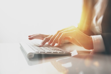 Closeup photo of female hands typing text on a keyboard. Visual effects, white background.