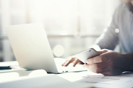 Foto de Businessman working with generic design notebook. Holding smartphone in hands - Imagen libre de derechos