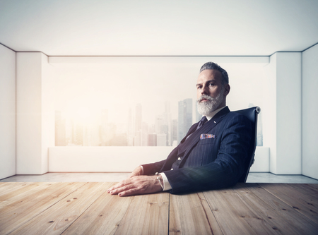 Foto de Portrait of adult businessman wearing trendy suit and sitting modern loft on leather chair against the panoramic window with city view. - Imagen libre de derechos