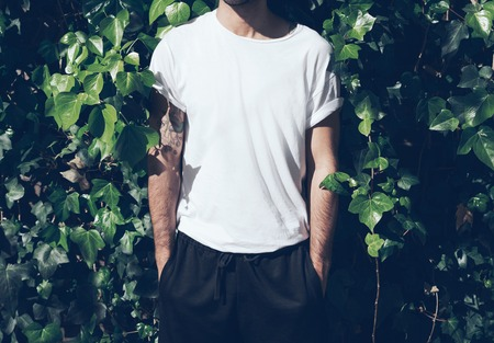 Bearded man with tattoo wearing blank white tshirt and black sunglasses.Green garden wall background.