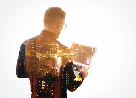 Double exposure  young bearded businessman wearing black shirt and holding contemporary notebook hands. Isolated white, night city background.