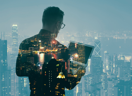 Photo for Double exposure young bearded businessman wearing black shirt and holding modern notebook hands. Panoramic view contemporary night city background. - Royalty Free Image