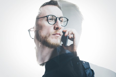 Photo pour Double exposure bearded banker wearing black shirt and glasses, holding contemporary smartphone hand. Isolated white, portrait man background. - image libre de droit