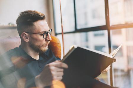 Foto de Portrait handsome bearded businessman wearing black shirt.Man sitting in vintage chairmodern loft studio, reading book and relaxing. Blurred background, film effect. - Imagen libre de derechos