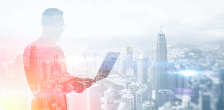 Photo pour Double exposure photo bearded businessman wearing black shirt and glasses.Banker holding contemporary notebook hands,work online banking.Panoramic view modern skyscraper city background. - image libre de droit