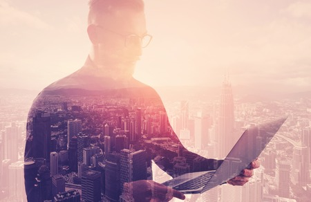 Photo for Double exposure businessman wearing black shirt and glasses.Banker holding contemporary notebook hands.Using work online banking system. Modern city sunset background. - Royalty Free Image