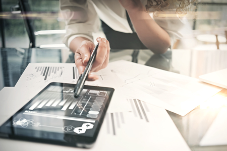 Investment department working process.Closeup photo business woman showing reports modern tablet screen.Statistics graphics screen.Banker holding pen for signs documents, new startup.