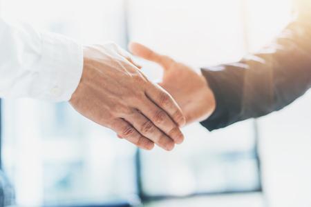 Business partnership meeting. Photo businessmans handshake. Successful businessmen handshaking after good deal. Horizontal, blurred