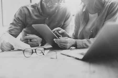 Coworking process. Photo young business crew working with new startup project.Notebook on wood table.Woman showing reports digital tablet,man holding document.Blurred background,black white.Horizontal