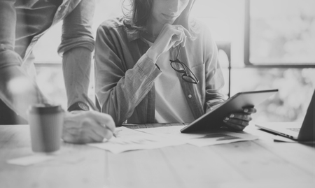 Account Managers Working Modern design Office.Woman Showing Market Report Digital Tablet.Producer Department Work New Startup Project.Researching Process Wood Table.Blurred Background.Black White