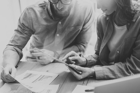 Photo Sales Manager Working Modern Studio.Woman Showing Market Reports Digital Tablet.Account Department Work New Startup Project.Researching Process Wood Table.Blurred Background.Black White