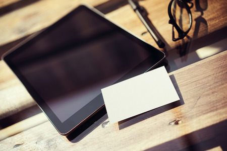 Photo pour Closeup Modern Tablet Blank Black Screen,Glasses Wood Table Inside Interior Coworking Studio Place.Empty Mockup Design White Business Card Corporate Message Background.Mock Up Private Objects Text - image libre de droit