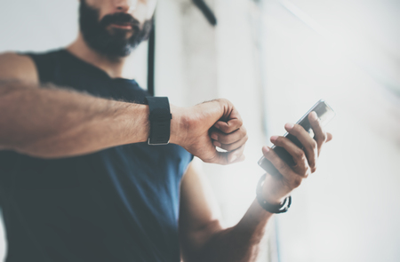 Photo for Close-up Shot Bearded Sportive Man After Workout Session Checks Fitness Results Smartphone.Adult Guy Wearing Sport Tracker Wristband Arm.Training hard inside gym.Horizontal bar background.Blurred - Royalty Free Image