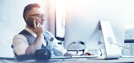 Foto per Closeup Bearded Businessman Wearing White Shirt Waistcoat Working Modern Loft Startup Desktop.Creative Young Man Use Smartphone Call Meeting Partner.Guy Work Office Thinking Business Strategy.Blurred - Immagine Royalty Free