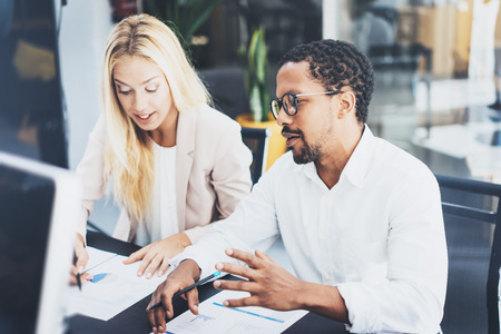 Two young coworkers working together in a modern office.Man wearing glasses and discussing with young woman new project.Horizontal,blurred background.