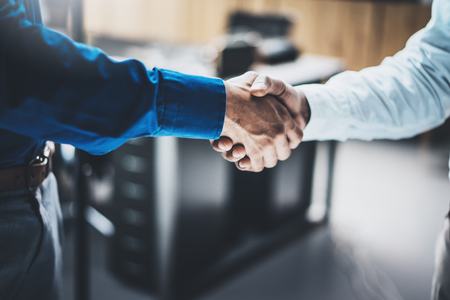 Business partnership handshake concept.Closeup photo of two businessmans handshaking process.Successful deal after great meeting.Horizontal, blurred background