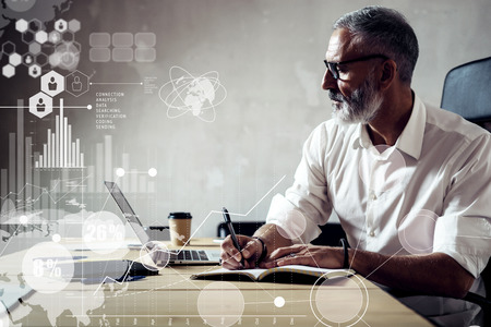 Foto de Concept of digital screen with global virtual icon,diagram, graph interfaces.Adult successful businessman wearing a classic glasses and working with laptop at the wood table in modern loft.Horizontal - Imagen libre de derechos