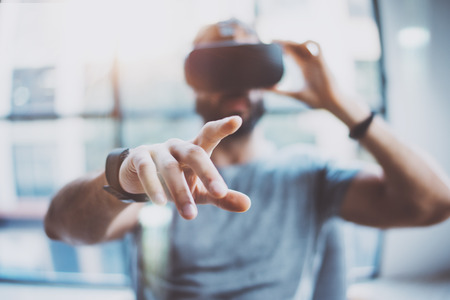 Foto de Closeup of male hand.Bearded young man wearing virtual reality goggles in modern coworking studio. Smartphone using with VR headset in office. Horizontal, blurred - Imagen libre de derechos