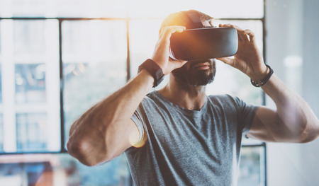 Photo pour Attractive bearded man enjoyingvirtual reality glasses in modern interior design coworking studio.Home play concept.Smartphone use with VR goggles headset. Horizontal,flare effect,blurred background - image libre de droit