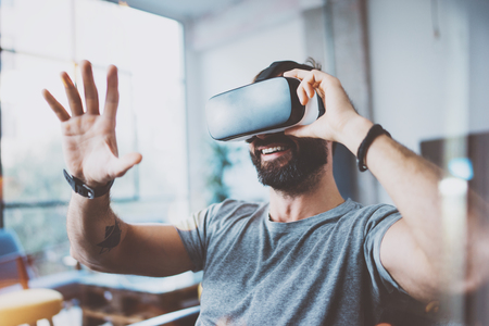 Photo pour Young bearded man wearing virtual reality glasses in modern interior design coworking studio. Smartphone using with VR goggles headset. Horizontal,flares effect, blurred background - image libre de droit