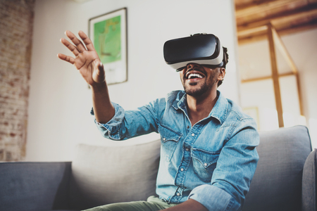 Photo pour Concept of technology,gaming,entertainment and people.Happy bearded african man enjoying virtual reality glasses while relaxing on sofa at home.Blurred background. - image libre de droit