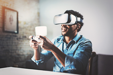 Photo pour Concept of technology,gaming,entertainment and people.African man enjoying virtual reality glasses while relaxing in living room.Happy young guy with VR headset playing video game at home.Blurred. - image libre de droit