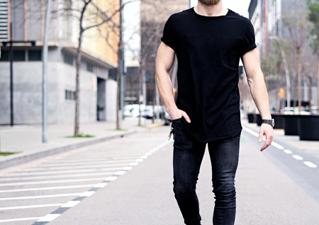 Closeup view of young muscular man wearing black tshirt and jeans walking on the streets of the modern city. Blurred background. Hotizontal mockup.