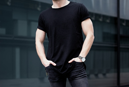 Young caucasian muscular man wearing black tshirt and jeans posing in center of modern city. Blurred background. Hotizontal mockup.