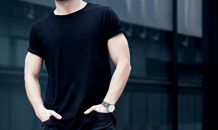 Closeup of young caucasian muscular man wearing black tshirt and jeans posing in center of modern city. Blurred background. Hotizontal mockup.