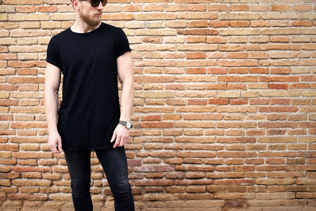Young muscular man wearing black tshirt,sunglasses and jeans posing outside. Empty brown grunge brick wall on the background. Hotizontal mockup.