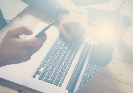 Businessman working at the wood table with laptop.Man holding smartphone at hand and texting message.Horizontal, visual effects.