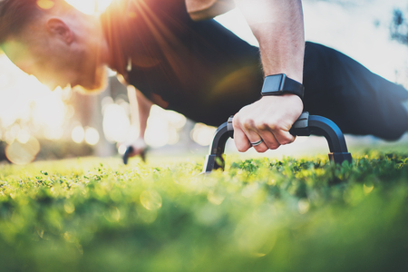 Foto de Healthy lifestyle concept.Training outdoors.Handsome sport man doing pushups in the park on the sunny morning. Blurred background. - Imagen libre de derechos