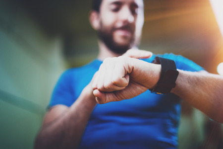 Photo pour Young smiling athlete checking burned calories on electronic smart watch application after good indoor workout session in fitness gym.Blurred background.Flares effect. - image libre de droit