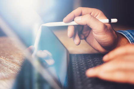 Photo pour Man using contemporary electronic tablet keyboard-dock station while sitting at the wooden table at office.Men using digital stylus pointing to device screen.Blurred background. Horizontal closeup. - image libre de droit