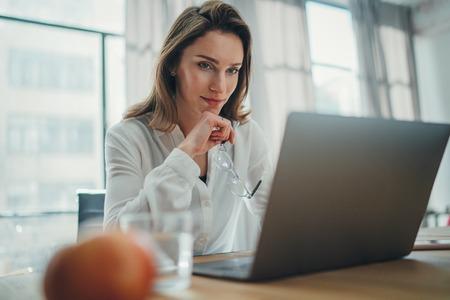 Foto de Handsome businesswoman working on laptop at her workplace at modern office.Blurred background. - Imagen libre de derechos