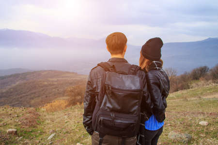 Photo pour A guy with a backpack and a girl looking at the mountains in the distance, the concept of tourism. - image libre de droit
