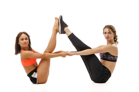 Photo pour Two young girls are engaged in stretching on a white background. - image libre de droit