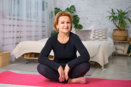 Foto de Mature woman in a black tracksuit doing yoga sitting on the Mat at home, against the background of a bed and pots of green plants, healthy lifestyle concept sitting at home - Imagen libre de derechos